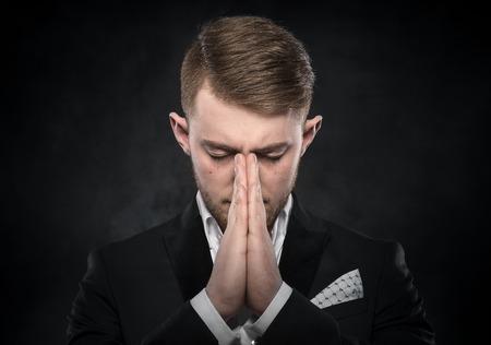 reverent: Portrait of businessman praying or thinking over dark background. Stock Photo