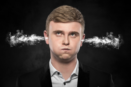 stressful: Stressful man with smoke or fume coming out from his ears on dark background. Stock Photo
