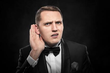 big ear: Man with big ear listening something on a dark background. Stock Photo
