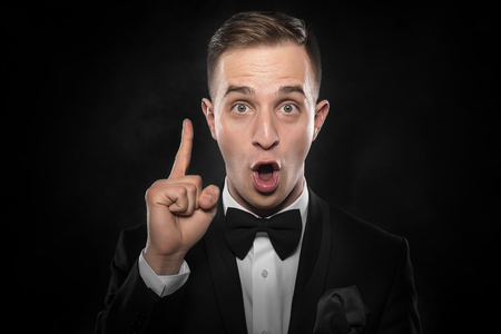 darck: Idea. Young man shows finger up over darck background. Stock Photo