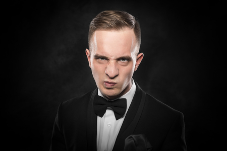 frowned: Elegant angry young man in suit looking frowning on dark background.