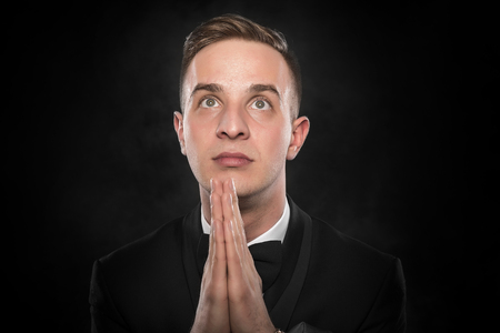 wishful: Portrait of businessman praying or thinking over dark background. Stock Photo