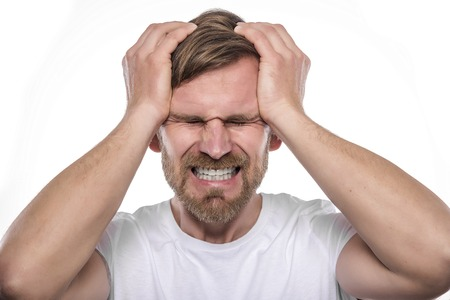 screaming head: Depressed young man holding his head and screaming.