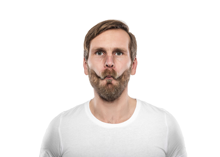 illogical: Man in white T-shirt grimaces. Isolated on white. Stock Photo