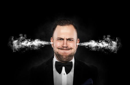 fume: Stressful man with smoke or fume coming out from his ears on dark background. Stock Photo