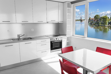 down lights: Modern white kitchen interior with lake view in the window.