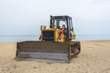 consolidate: Yellow old tractor on a sandy sea beach. Stock Photo