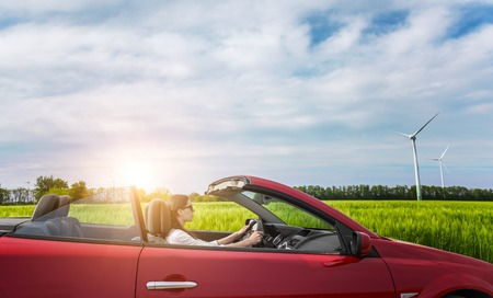 Girl in red cabriolet in a field with wind turbines at sunset.
