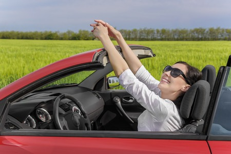 smiley face car: Happy woman resting at the wheel of a car on a country road at sunset. Vacation or travel concept. Stock Photo