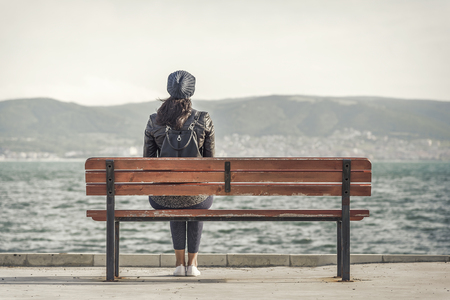 lonelyness: Woman sitting on the bench near the sea.