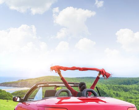 automobiles: Girl in a red convertible car on a background seascape with a shawl waving in the wind. Stock Photo