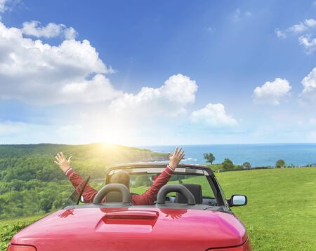 Man in a convertible car relaxes and enjoys the freedom on the country road by the sea. Travel or vacation concept.