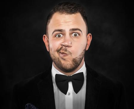 skeptical: Portrait of a skeptical businessman over dark background.