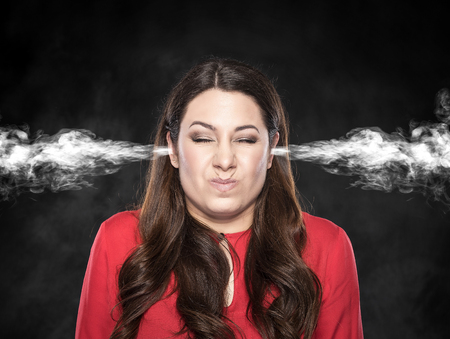 aggravated: Smoke from the ears of a woman on a dark background. Overvoltage - concept.