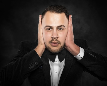 Man in suit covering his ears over dark background. Stock Photo