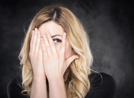 Donna che pigola attraverso le dita su sfondo scuro