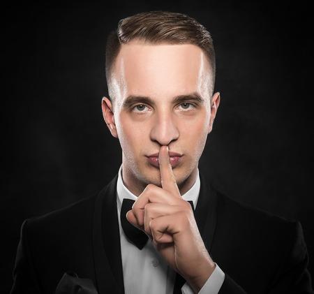 shush: Man gesturing silent on a dark background.