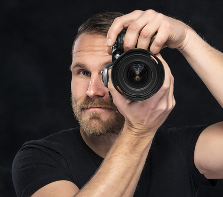 darck: Photographer man with camera on darck background.