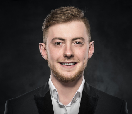 black eye: Young handsome man in suit smiling on dark background.
