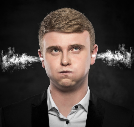 aggravated: Stressful man with smoke or fume coming out from his ears on dark background. Stock Photo