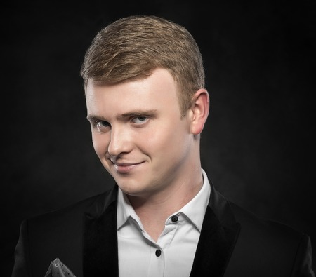 business skeptical: Portrait of a funny man over dark background.