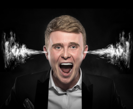 fume: Angry man with smoke or fume coming out from his ears on dark background.