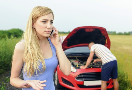empty tank: Young blonde woman call for help on the phone. Young couple can not continue the way because of the broken car. Damage to auto.