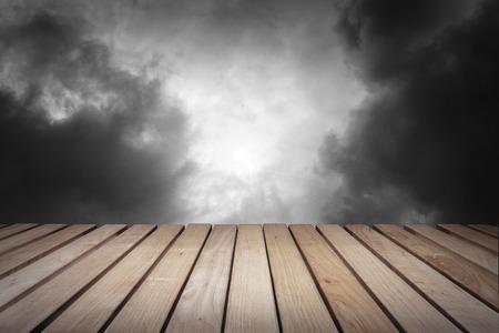 Wood platform and cloudy dark dramatic sky.