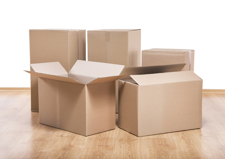 downsize: Empty room with a white wall and moving boxes on the floor. Stock Photo