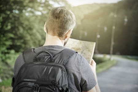man searching: Traveler man searching right direction on map, freedom and active lifestyle concept