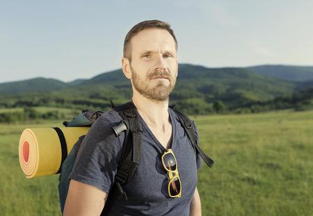 Attractive male hiker on hillside on sunset.