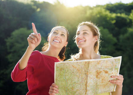 Holidays and tourism concept - beautiful girls with map in the rural Stock Photo