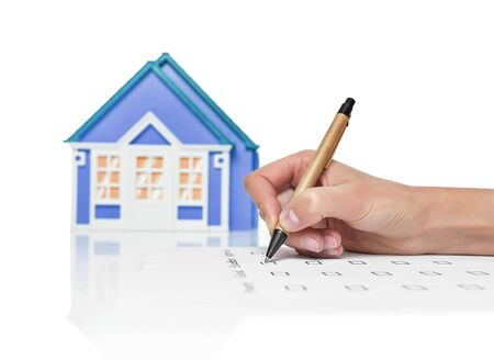 Image of a female signing a deed of sale, mortgage document or insurance contract on a house with a closeup view of his hand with a small model of a house. Stock Photo