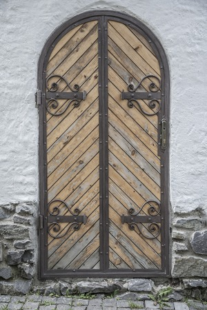 old wooden door: Old wooden door with wrought iron and bolts. Stock Photo