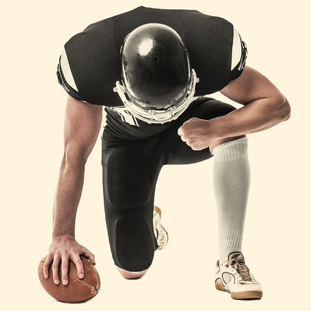 crouches: American football player on white background. Toned photo.