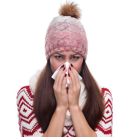 Runny nose of the girl in winter clothes. Isolated on white.