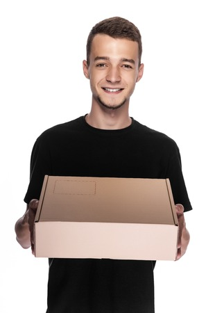 cardbox: Smiling young delivery man holding and carrying a cardbox isolated on white background Stock Photo