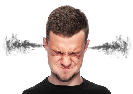 Angry man with smoke or fume coming out from his ears on white background. Stock Photo