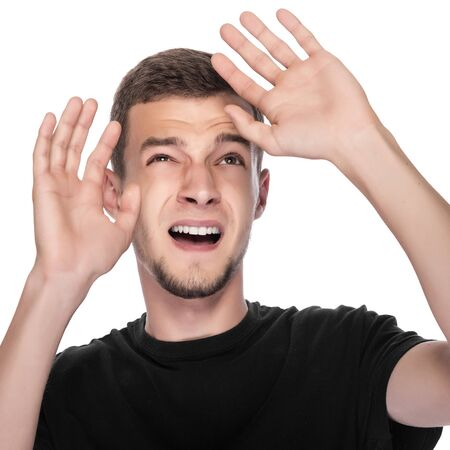 concealed: Young man in fear of concealed hands. On white. Stock Photo