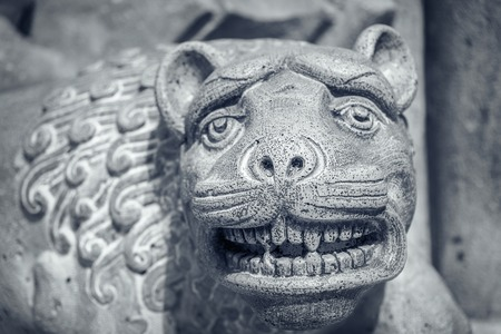 Ancient sculpture of a lion or tigers head.