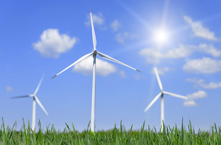 Wind power energy. Green field and wind turbines generating electricity. Stock Photo