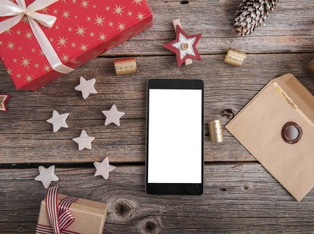 Smartphone on a wooden table with a variety of Christmas decorations.