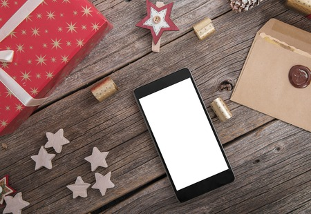 toygift: Smartphone on a wooden table with a variety of Christmas decorations.