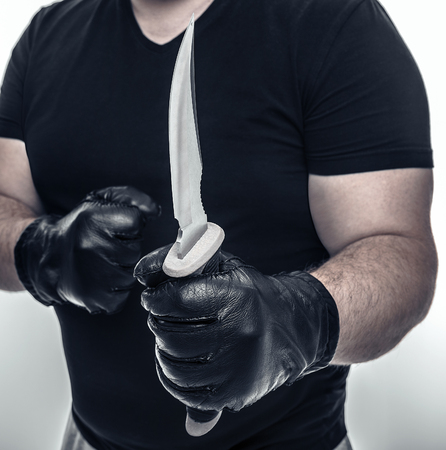male killer: Man with athletic hands holding a military knife. Close-up.