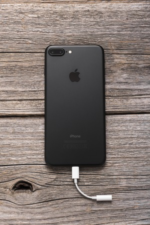 mini jack: UZHGOROD, UKRAINE - DECEMBER 20, 2016: New black iPhone 7 Plus from the company Apple, and a new adapter with lightning to mini jack 3.5 mm., on wooden background.