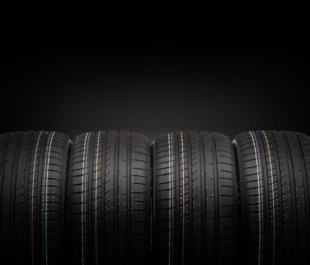 winter tires: Car tires on a dark background. Stock Photo