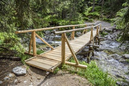 Wooden bridge across a fast mountain river.