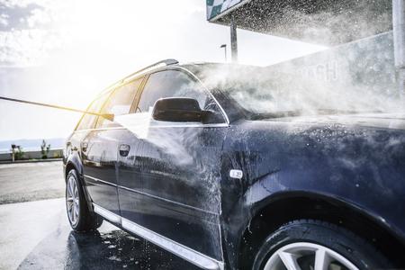 Hogedrukwasauto buitenshuis. Auto wassen onder de blote hemel. Stockfoto