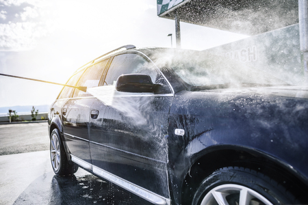 High-pressure washing car outdoors. Car washing under the open sky. Archivio Fotografico