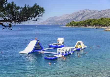 Aquapark on the sea with resting tourists in Brela, Croatia.